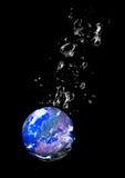Planetenerde, die in Wasser sinkt lizenzfreie stockfotografie
