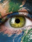 Planetjord och grönt mänskligt öga royaltyfria bilder
