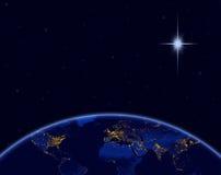 Planetjord och julstjärna i natthimmel Arkivbilder