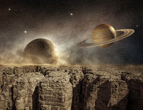 Planets in the sky of a barren landscape. Saturn and moon in the sky of a barren landscape Stock Photo