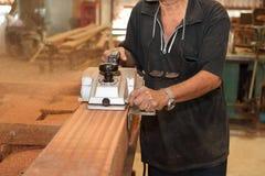 Planeuse électrique rasant un morceau de conseil en bois avec des mains de charpentier supérieur dans l'atelier de menuiserie Foy Photo libre de droits