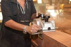 Planeuse électrique rasant un morceau de conseil en bois avec des mains de charpentier supérieur dans l'atelier de menuiserie Foy Photographie stock