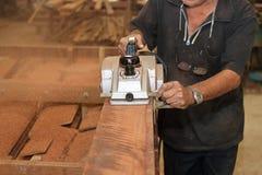 Planeuse électrique rasant un morceau de conseil en bois avec des mains de charpentier supérieur dans l'atelier de menuiserie Foy Image libre de droits