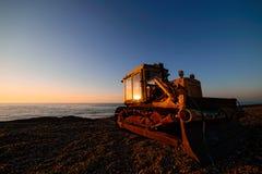 Planierraupe auf Strand bei Sonnenaufgang Stockfotografie