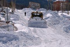 Planierraupe säubert die Straße, vom Schnee im Dorf Lizenzfreies Stockfoto