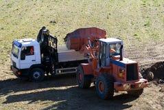 Planierraupe und LKW bei der Arbeit Stockbilder