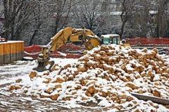 Planierraupen-Gräber während der Arbeit mit vielen Felsen und Lots fre stockfotos