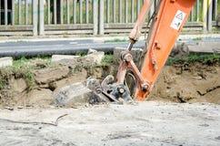 Planierraupenbaggermaschinerie, die einen Abzugsgraben auf der Straße für die neue Rohrleitung gräbt Lizenzfreie Stockbilder