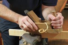 Planierung einer Holzleiste mit einem Hobel Stockfoto