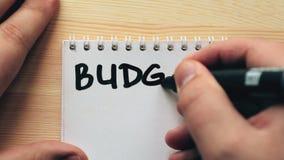Planierungskonzept des Budgets Notizblock, Mannschreibens-Wort Budget, hölzerner Hintergrund stock footage