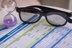 Planificación de la jubilación con los vidrios y el reloj de arena, concepto del negocio Foto de archivo libre de regalías