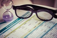 Planificación de la jubilación con los vidrios y el reloj de arena, concepto del negocio Imágenes de archivo libres de regalías