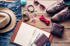 Planificación para la ropa y los accesorios del viaje en el piso de madera Fotografía de archivo