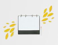 Planificador abierto del día con los pétalos y el lápiz amarillos, en fondo gris Endecha plana Espacio de trabajo con la hoja a c Fotografía de archivo