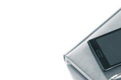 Planificador con el teléfono en un fondo blanco aislante Imagen de archivo libre de regalías