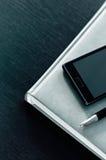 Planificador con el teléfono en un fondo negro Fotos de archivo libres de regalías