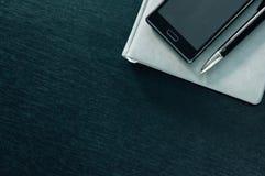 Planificador con el teléfono en un fondo negro Imágenes de archivo libres de regalías