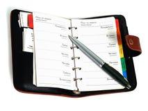 Planificador semanal sobre blanco imagen de archivo