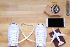 Planification économisante pour le budget de voyage du concept de vacances, des chaussures blanches d'espadrilles et de l'avion s photos libres de droits