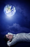 Planing his future on earth. Young man dreaming to his future on earth stock photo