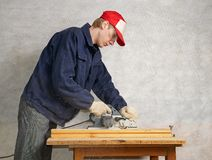 Planing the wood. The worker operates electric planer Stock Images