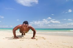 Plank at the beach. Black man does plank at the beach royalty free stock images