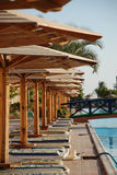 Plank beds under umbrellas at pool in hotel. Egypt Royalty Free Stock Photos