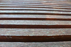 Plank benches. Brown wooden plank benches that go the distance Stock Photos