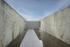 Plank concrete pattern wall and pale timber pathway with sky background. Plank concrete pattern wall and pale timber pathway along with gravel pond and sky stock images