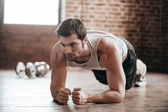 Plank it!. Confident muscled young man wearing sport wear and doing plank position while exercising on the floor in loft interior stock image