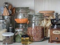 Plank in de keuken met diverse kruiken van graangewassen en keukengereedschap Glaskruiken met deegwaren, linzen, kouskous, bonen  royalty-vrije stock fotografie