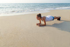 Plank exercise on the beach. Young woman is doing plank exercise on the beach royalty free stock photo