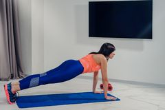 Plank exercise with dumbbells. Beautiful slim sporty woman doing plank exercise with dumbbells stock images