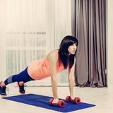 Plank exercise with dumbbells. Beautiful slim sporty woman doing plank exercise with dumbbells, image with warm vintage toning royalty free stock photos