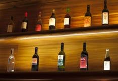 Plank met de flessen van de glaswijn en zachte lichten binnen een wijnmakerij Stock Foto's