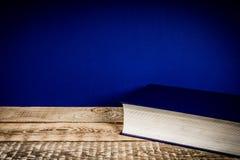 Plank met een boek en een blauwe muur Royalty-vrije Stock Foto