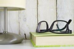 Plank met glazen op een boek en een lamp, klaar voor lezingstijd Stock Afbeeldingen