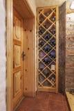 Plank met wijnflessen in huis Royalty-vrije Stock Afbeeldingen