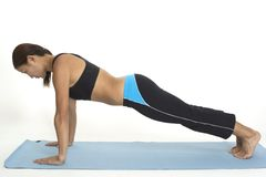 Plank Pose 1. A female fitness instructor demonstrates the starting position of the plank pose stock images