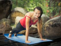 Plank pose. Woman is practicing yoga outdoor. Plank pose Royalty Free Stock Photo