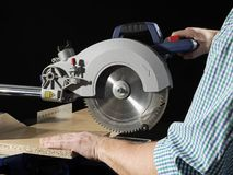 Plank sawing. Carpenter cutting flaxboard using sliding compound mitre saw Stock Photo