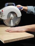 Plank sawing. Carpenter cutting flaxboard using sliding compound mitre saw Stock Images