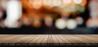 Plank Wood table top with blur nightclub bar counter with bokeh. Light background,banner mock up for display of product or design content stock photo