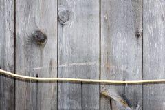 Planka (bräde) och elektrisk kabel gammalt och sprucket Arkivfoton