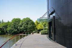 Planked bana mellan det moderna byggnad och dammet i solig sommar Arkivfoton
