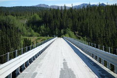 A planked bridge spanning a large river. Royalty Free Stock Photo