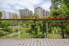 Planked footbridge over creek in modern city on cloudy summer da Royalty Free Stock Images