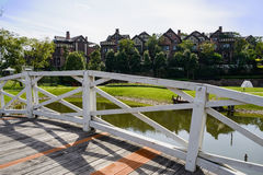 Planked footbridge over lake before houses in sunny autumn after Royalty Free Stock Photo