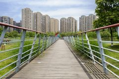 Planked footbridge with railings before storied apartments in su Royalty Free Stock Photo