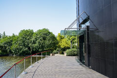 Planked path between modern building and pond in sunny summer Stock Photos